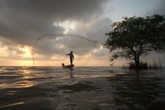 Sylwetka rybacy rzuca sieci ryba na zmierzchu czasie Fotografia Stock