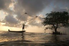 Sylwetka rybacy rzuca sieci ryba na zmierzchu czasie Zdjęcie Royalty Free