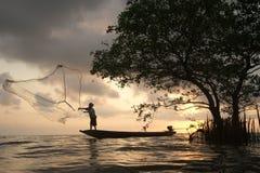 Sylwetka rybacy rzuca sieci ryba na zmierzchu czasie Obraz Stock