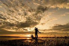 Sylwetka rybacy z zmierzchu czasem przy Wanon Niwat okręgiem Zdjęcia Stock