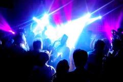 Sylwetka saksofonista otaczający mnóstwo ludźmi pod neonowymi światłami i światło reflektorów zdjęcia stock