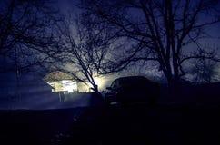 Sylwetka samochód i drzewa przy noc lasem z mgłą, surrealistycznych świateł mistyczny krajobraz Fotografia Stock