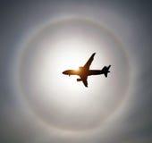 Sylwetka samolot w nieba słońcu i halo w chmurach Obraz Stock