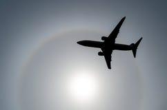 Sylwetka samolot w nieba słońcu i halo w chmurach Zdjęcie Stock