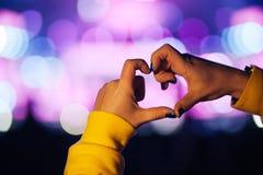 Sylwetka serce kształtujący tłum widownia przy żywym koncertem i ręki, lekki iluminujący jest władzą muzyka koncert Fotografia Royalty Free