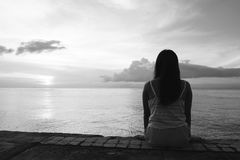 Sylwetka siedzi samotnie na tylnej stronie plenerowej piękna kobieta zdjęcie stock