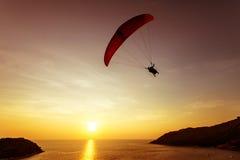 Sylwetka skydiver lata na tło zmierzchu morzu i niebie Zdjęcia Royalty Free