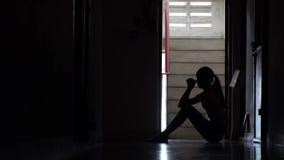 Sylwetka smutny młodej dziewczyny obsiadanie w zmroku opiera przeciw ścianie w starym mieszkaniu własnościowym, przemoc domowa, r zdjęcie wideo