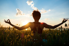 Sylwetka sportive dziewczyny ćwiczy joga w polu przy wschodem słońca obraz stock