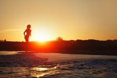 Sylwetka sportowy dziewczyna bieg wzdłuż plaży na zadziwiającym pomarańczowym zmierzchu tle Zdjęcia Royalty Free