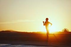 Sylwetka sportowy dziewczyna bieg wzdłuż plaży na zadziwiającym pomarańczowym zmierzchu tle Obrazy Royalty Free