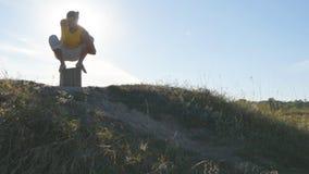 Sylwetka sporty mężczyzna obsiadanie przy joga pozą plenerową Jogowie ćwiczy joga ruszają się i ustawiają w naturze atleta Zdjęcia Stock