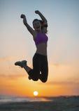 Sylwetka sprawności fizycznej młodej kobiety doskakiwanie na plaży przy półmrokiem Obraz Stock