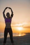 Sylwetka sprawności fizycznej młodej kobiety rozciąganie na plaży przy półmrokiem Zdjęcia Royalty Free