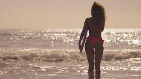 Sylwetka surfingowiec dziewczyny pozycja z kipieli deską na plaży przy zmierzchem Dziewczyny zmierzchu szczęśliwy patrzeje mienie zdjęcie wideo