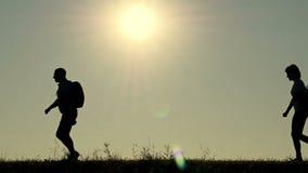 Sylwetka szczęśliwa rodzina turyści biega z plecakami podczas zmierzchu, jeden po drugim, zbiory