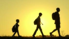 Sylwetka szczęśliwa rodzina turyści chodzi wzdłuż wierzchołka góra przy zmierzchem Ojciec i jego dwa syna iść zbiory