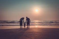 Sylwetka szczęśliwa rodzina z dziećmi przy zmierzchu morzem Arambo Zdjęcia Royalty Free