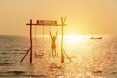 Sylwetka szczęśliwi ludzie bawić się huśtawkę nad morzem z lato znakiem Szcz??liwy wakacje poj?cie zdjęcie royalty free
