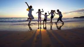 Sylwetka szczęśliwi ludzie bawić się na plaży przy zmierzchu czasem który zbiory