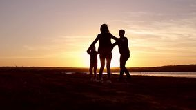 Sylwetka, szczęśliwy dziecko z matką i ojciec, rodzina przy zmierzchem, lato Biega, podnoszący dziecka w powietrzu, uściśnięcia,  zbiory wideo