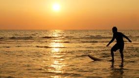 Sylwetka szczęśliwy kipiel mężczyzna surfing z długimi kipieli deskami przy zmierzchem na tropikalnej plaży zdjęcia royalty free