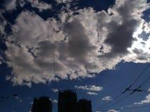 Sylwetka trzy drapacza chmur przeciw niebieskiemu niebu z białymi chmurami Zdjęcia Royalty Free