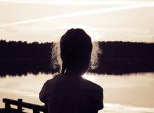 Sylwetka urocza mała dziewczynka na jeziorze przy zmierzchem stonowany Zdjęcie Royalty Free
