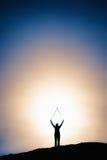 Sylwetka wizerunek mężczyzna z rękami podnosić przy wzrostem obraz royalty free