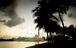 Sylwetka wizerunku pojęcia kokosowy drzewo przy brzeg jeziora z pięknym meczetu i zmierzchu tłem Obrazy Stock