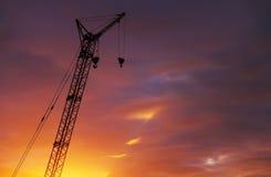 Sylwetka wysoki żuraw z dwa haczykami na zmierzchu niebie Obrazy Royalty Free