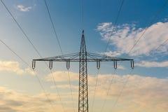 Sylwetka wysoki woltażu maszt przy chmurnym niebem przy zmierzchem Fotografia Stock