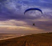 Sylwetka zasilanego paraglider strzelisty lot nad morzem przeciw zmierzchu niebu zdjęcia stock