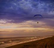 Sylwetka zasilanego paraglider strzelisty lot nad morzem przeciw zmierzchu niebu zdjęcie royalty free