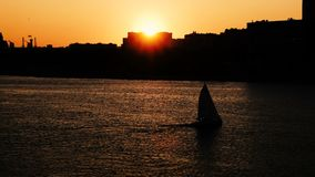 Sylwetki żeglowania łódź unosi się na rzece przy zmierzchem słońce sety za domem zdjęcie wideo