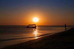 Sylwetki łodzie i mężczyzna przy zmierzchem Fotografia Stock