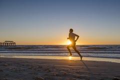Sylwetki atlety biegacza młody dynamiczny mężczyzna z dysponowanym silnym ciała szkoleniem na lato zmierzchu plaży biegać bosy w  Zdjęcie Royalty Free