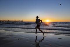 Sylwetki atlety biegacza młody dynamiczny mężczyzna z dysponowanym silnym ciała szkoleniem na lato zmierzchu plaży biegać bosy w  Fotografia Royalty Free