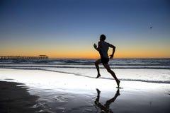Sylwetki atlety biegacza młody dynamiczny mężczyzna z dysponowanym silnym ciała szkoleniem na lato zmierzchu plaży biegać bosy w  Zdjęcia Stock