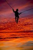 Sylwetki chłopiec trampolining wspaniały zmierzch Obrazy Royalty Free