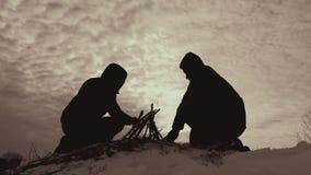 Sylwetki dwa facetów przyjaciele w drewnie w spadku, organizować obozują ogień, pomaga each inny, drużyny praca, dventures zbiory