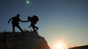 Sylwetki dwa mężczyzn pracy zespołowej turystów arywista wspina się górę chodząca turystyczna wycieczkuje przygoda arywistów zmie zdjęcie wideo