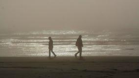 Sylwetki dwa persons chodzi w opposite kierunkach na Tillamook plaży, Oregon obraz stock