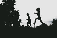 Sylwetki dzieciaki skacze od piasek falezy przy plażą Zdjęcie Stock