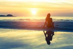 Sylwetki dziewczyny obsiadanie na plaży z odbiciem w wodzie Obraz Royalty Free