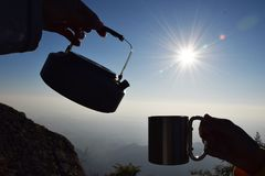 Sylwetki filiżanka przy wschód słońca z halnym tłem i czajnik fotografia royalty free