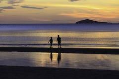 Sylwetki fotografia dwa brata cieszy się na plaży Zdjęcia Stock