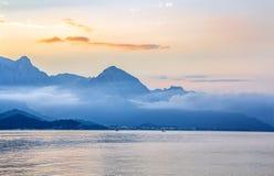 Sylwetki góry dennym wybrzeżem w zmierzchów promieniach Obraz Stock