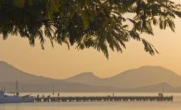 Sylwetki gałąź akacja, góra, molo, łodzie fotografia stock