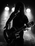 Sylwetki gitary akustycznej gracz na scenie zdjęcie stock
